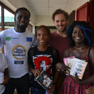 Kriterion Monrovia team members holding new DVDs with EWB-NL member Joost