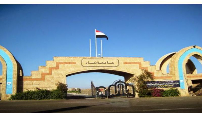 Entrance to Thamar university in Yemen. A stone gate with national flag above