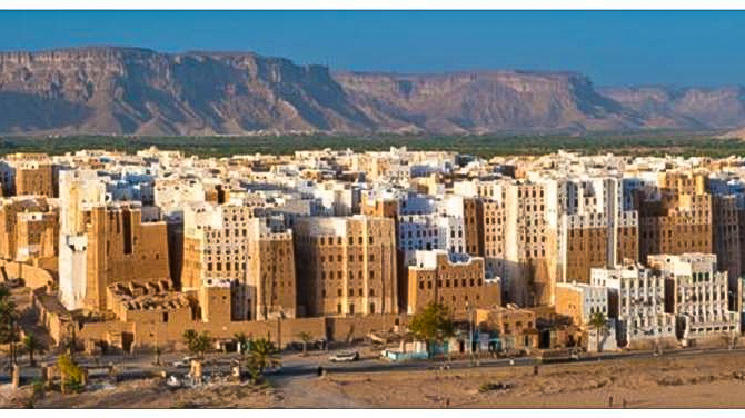 A wide angle view of Dhamar, Yemen with buildings and skyscrapers and mountains in the background.
